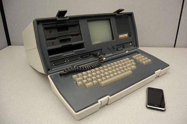 Foto de un iPhone y un enorme ordenador portátil de principios de los 80, de unos 20 kilos de peso
